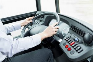 image of a bus driver at the steering wheel